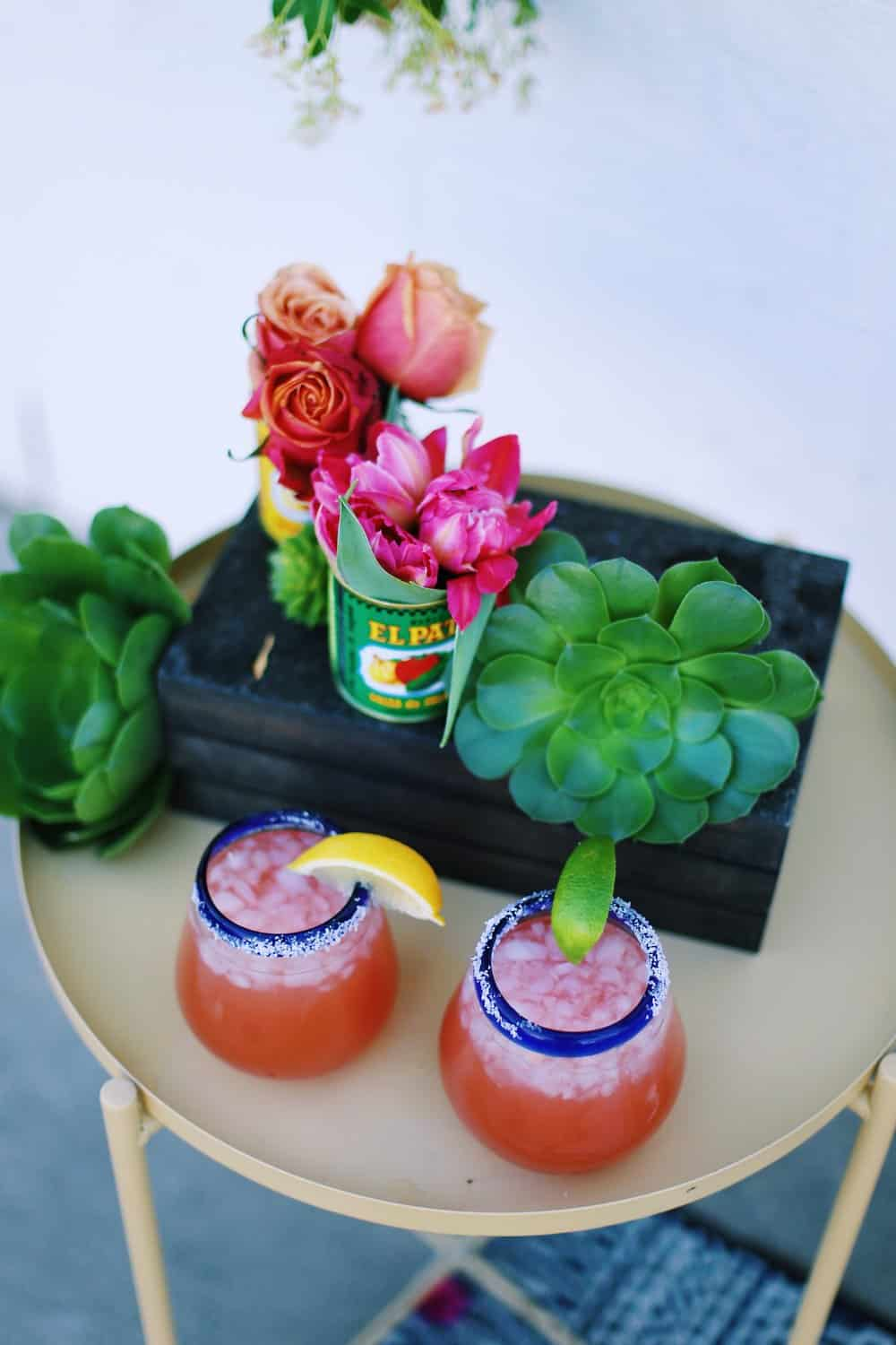 Two margaritas on the rocks with flowers in Mexican food cans on a beige table