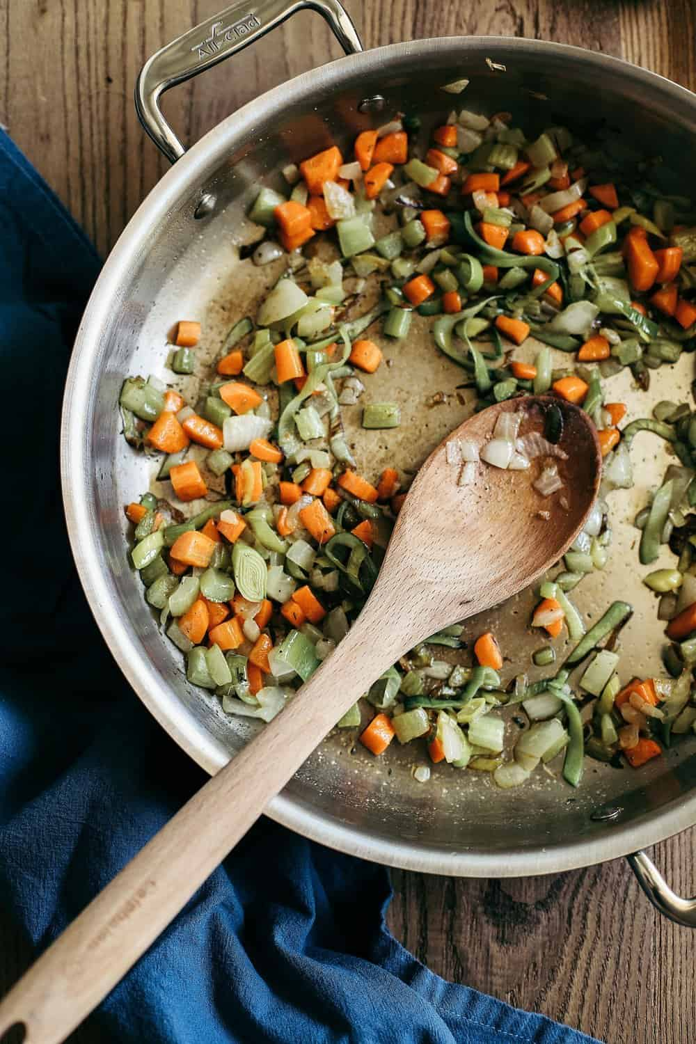Diced carrots, celery, leeks, and onions in a saute pan.
