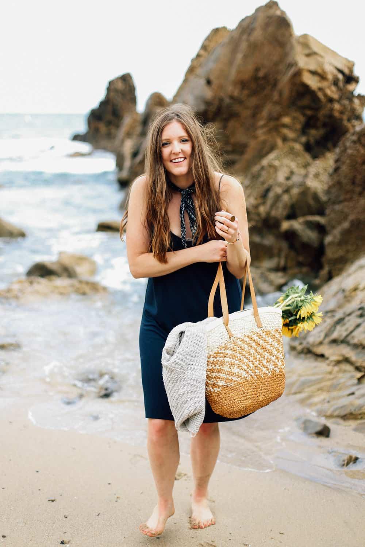 Elizabeth with a beach bag and flowers on the beach