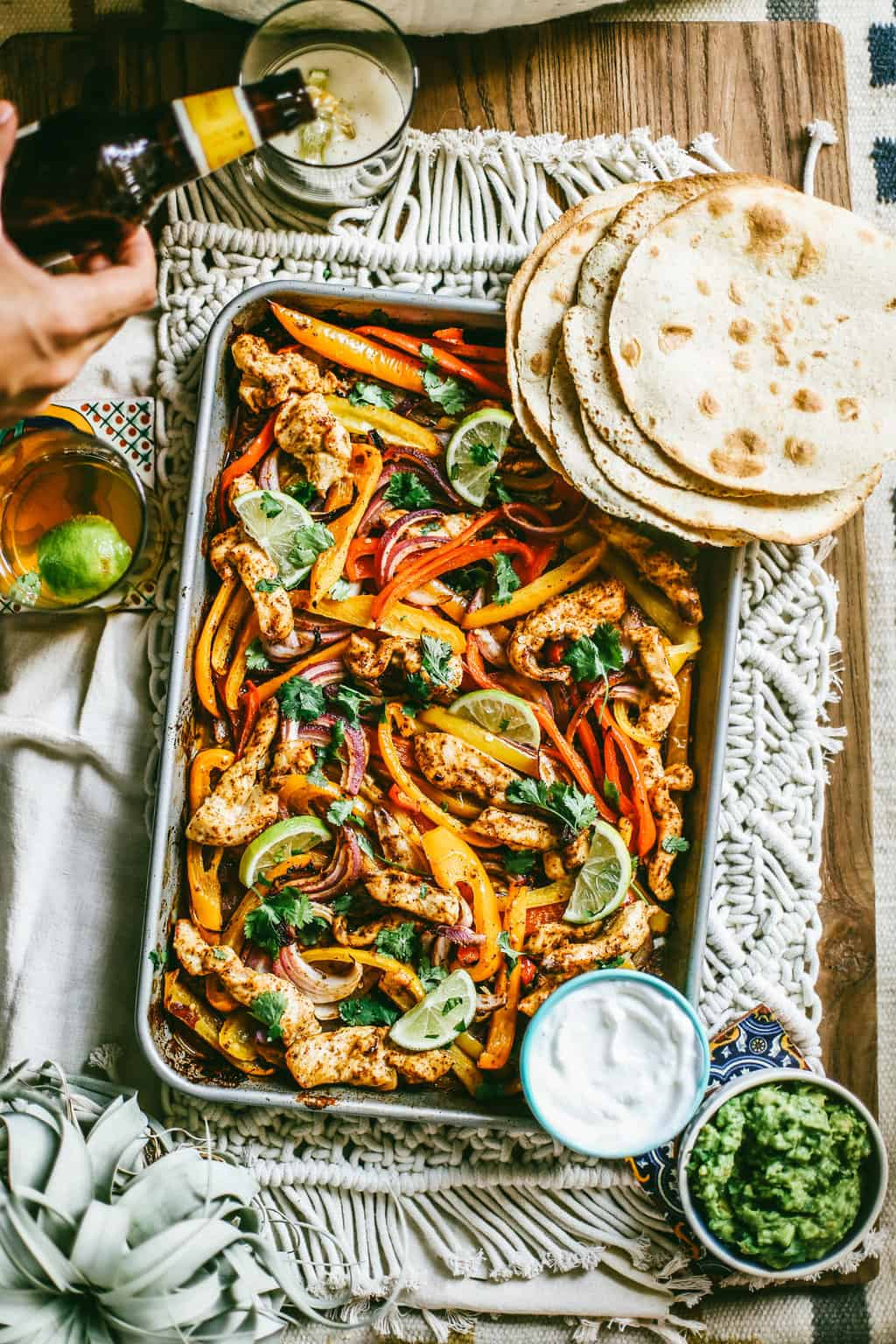 chili lime chicken and vegetables on a sheet pan with flour tortillas on the side