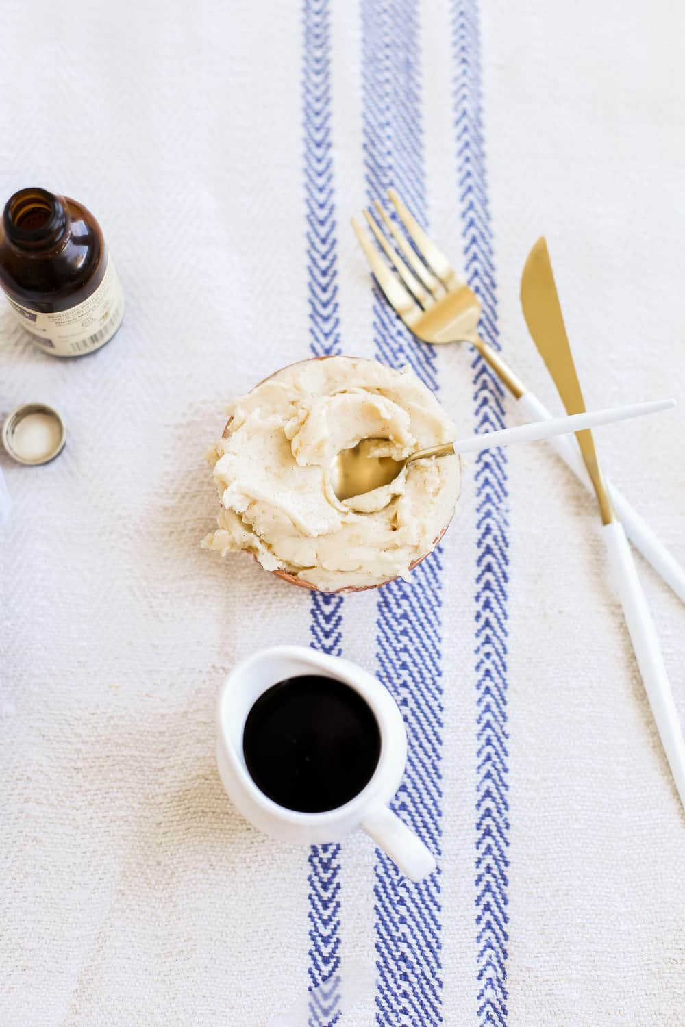 A bowl of whipped maple butter with a gold spoon in the bowl.