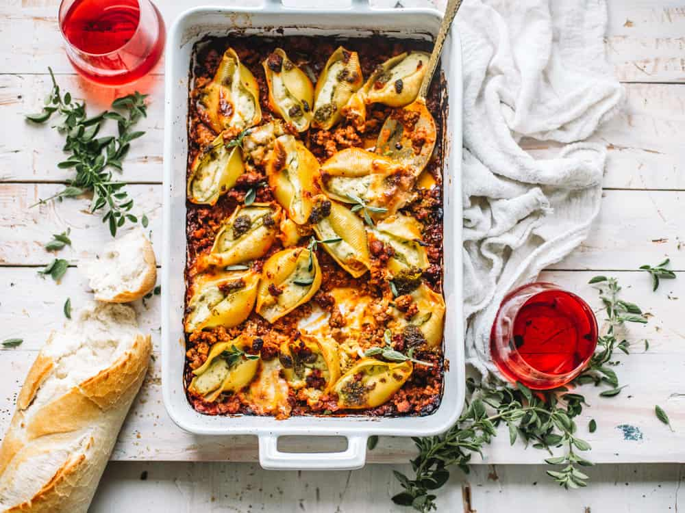 pesto stuffed shells with Italian sausage meat marinara in white casserole dish on white kitchen towel with spoon