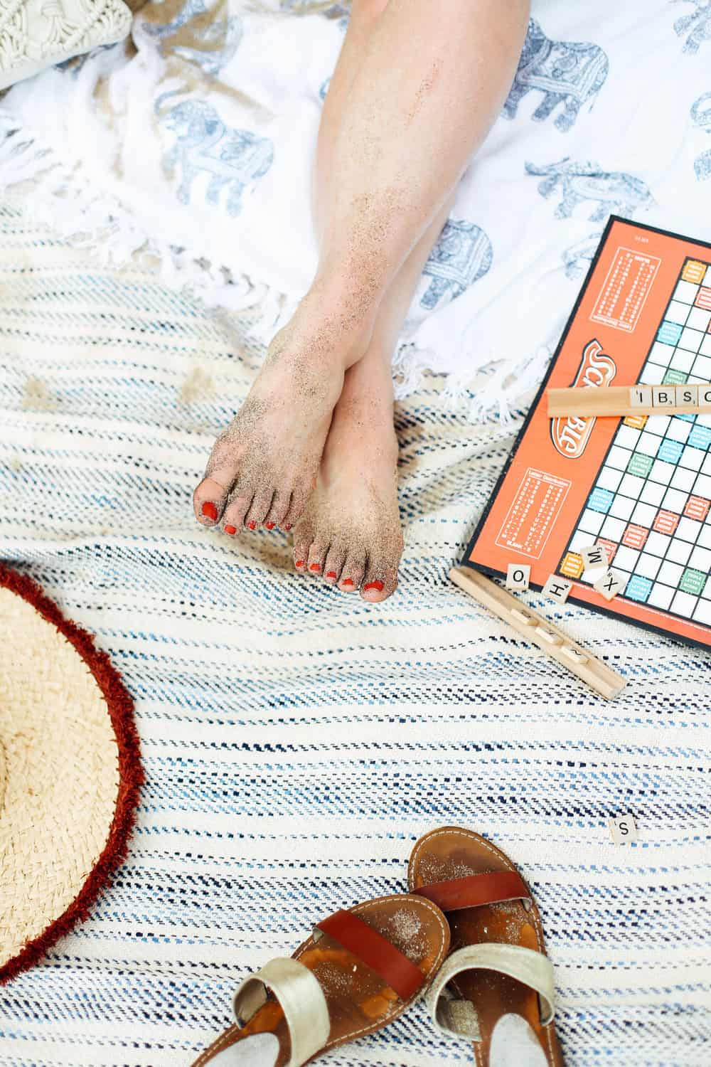 Sandy bare feet with Scrabble game board on beach towels