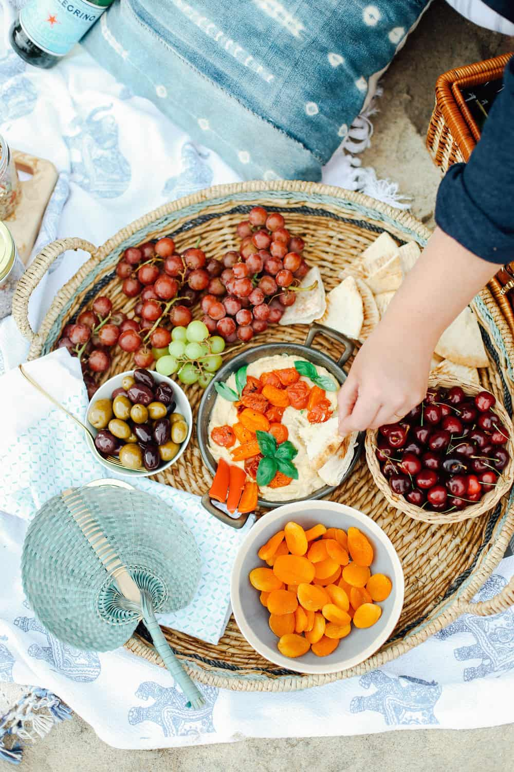 Hand dipping pita in a bowl of hummus in a wicker basket with grapes cherries apricots and olives on beach towels