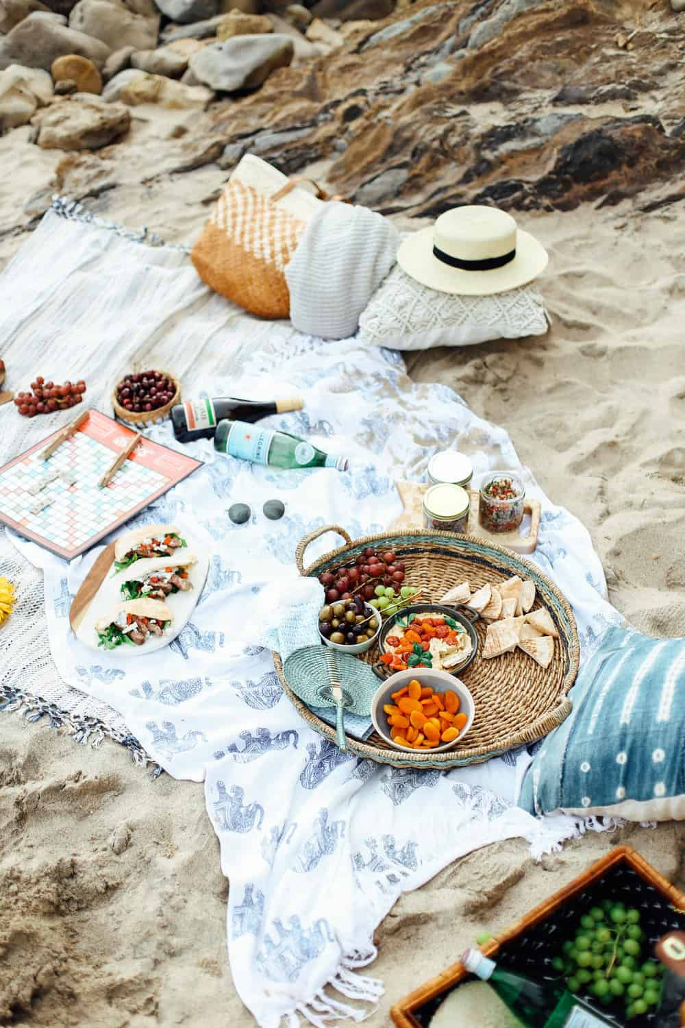 Mediterranean Beach Picnic food and drinks in a wicker basket on beach towels at the beach