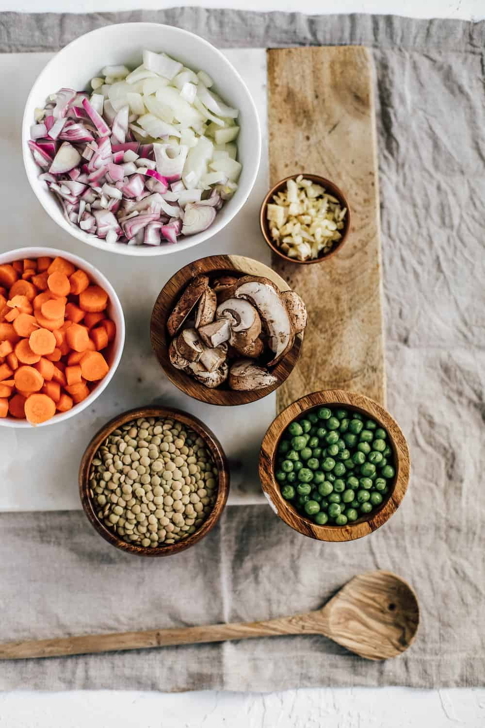 Small wooden bowls of lentils, peas, mushrooms, carrots, and diced onions.