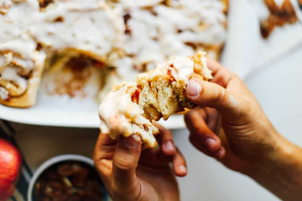A apple pecan cinnamon roll being ripped apart.