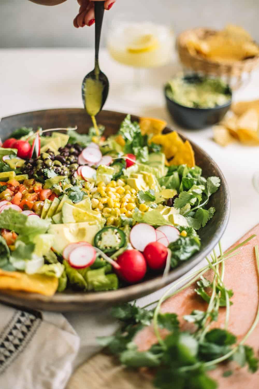 A big wooden bowl of a Chopped Tostada Salad with Avocado Cilantro Dressing