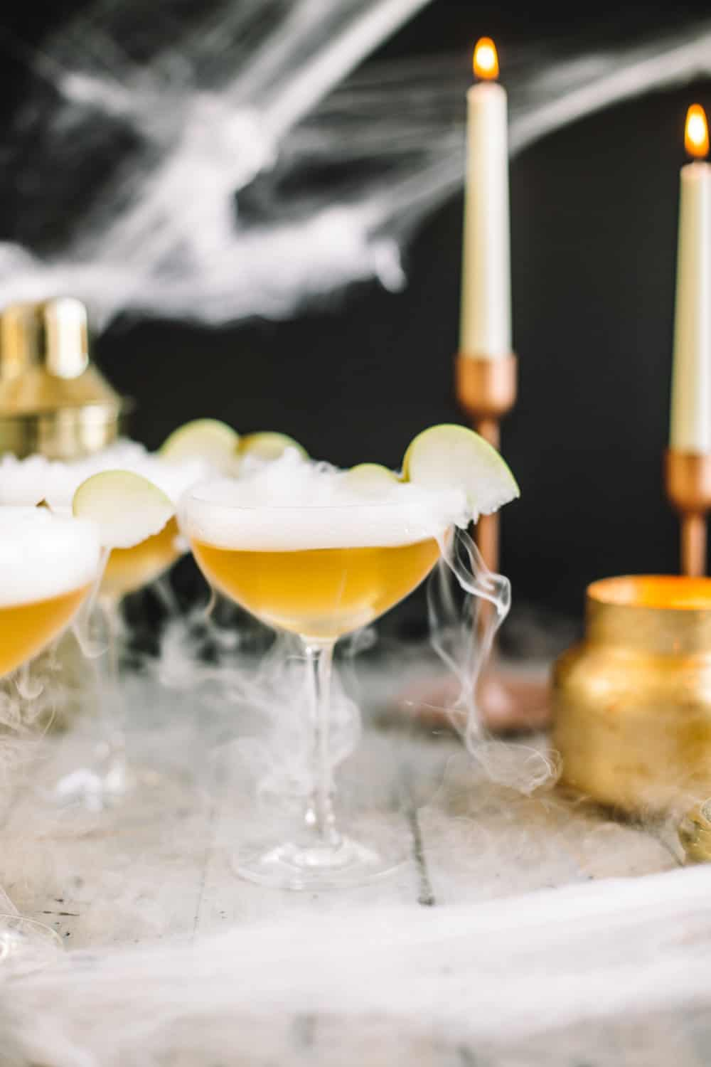 Elderflower wand martini garnished with dry ice and a sliced apple.