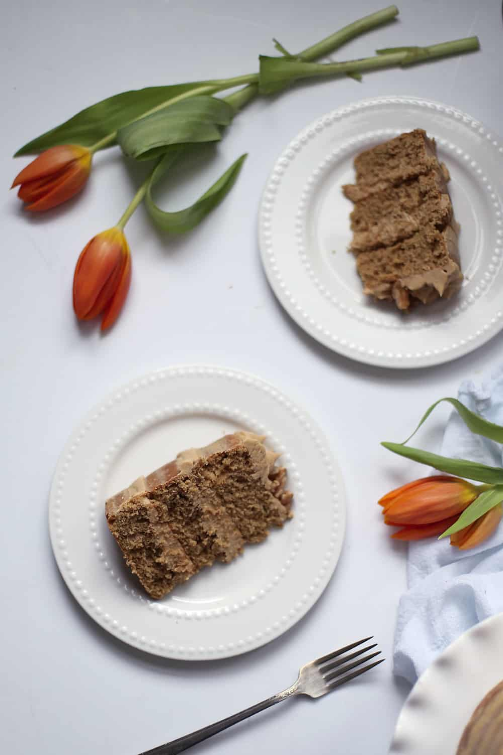 two slices of coffee walnut cake on white plates with orange tulips.