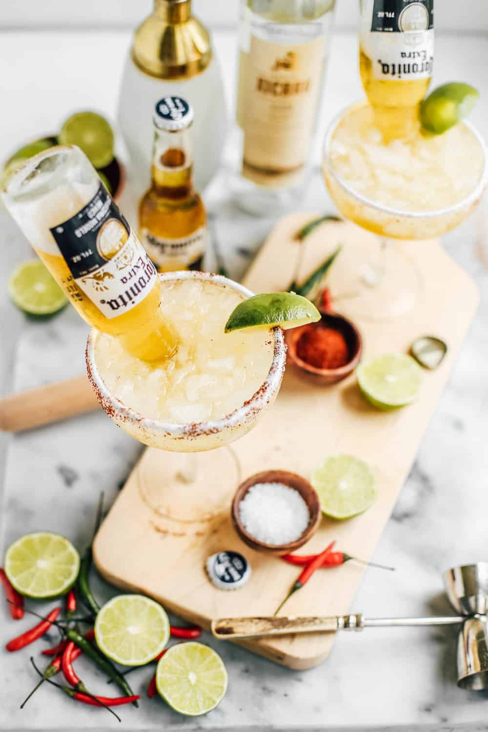 Lime and Chili Mezcal Beergaritas in glasses with Coronitas on a wooden board