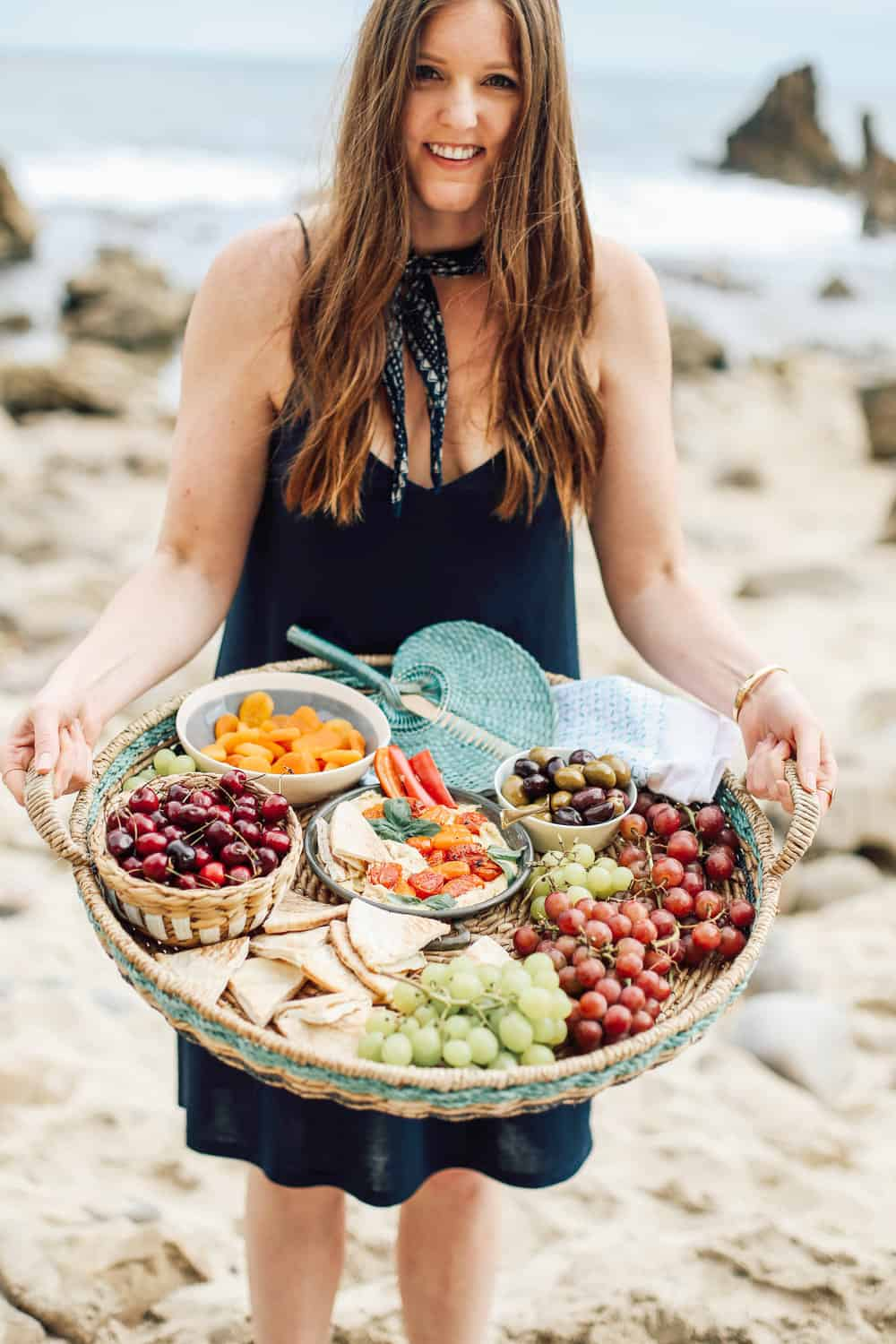 Elizabeth holding a wicker basket full of grapes pita cherries apricots olives and hummus on the beach