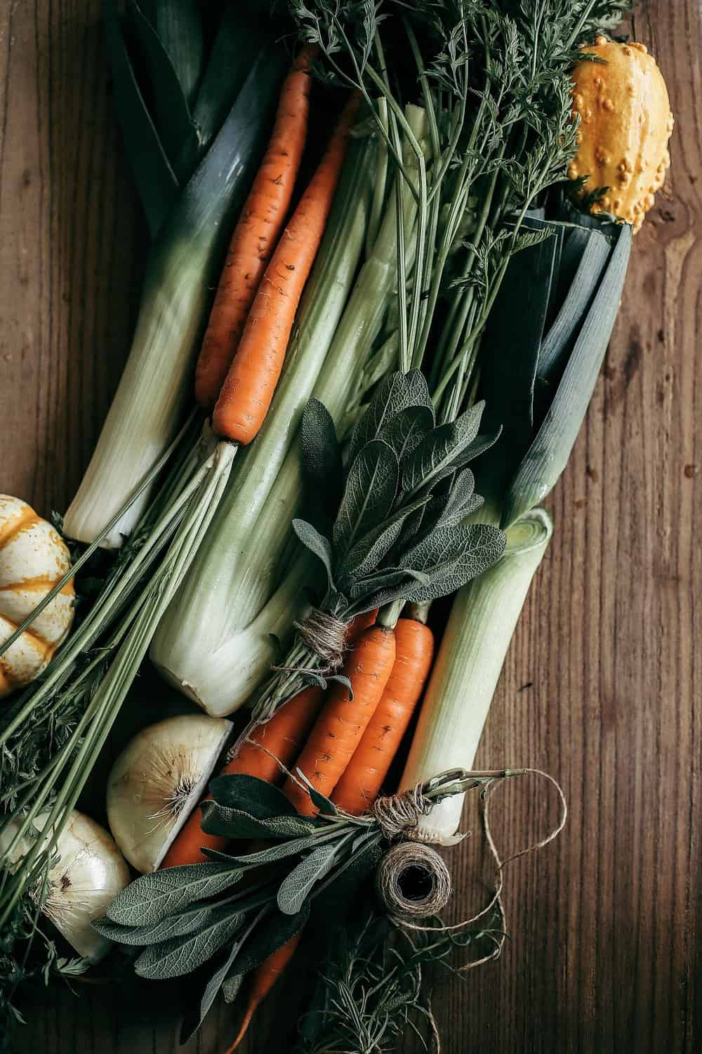 Celery, carrots, leeks, onion, and sage on a wooden cutting board.