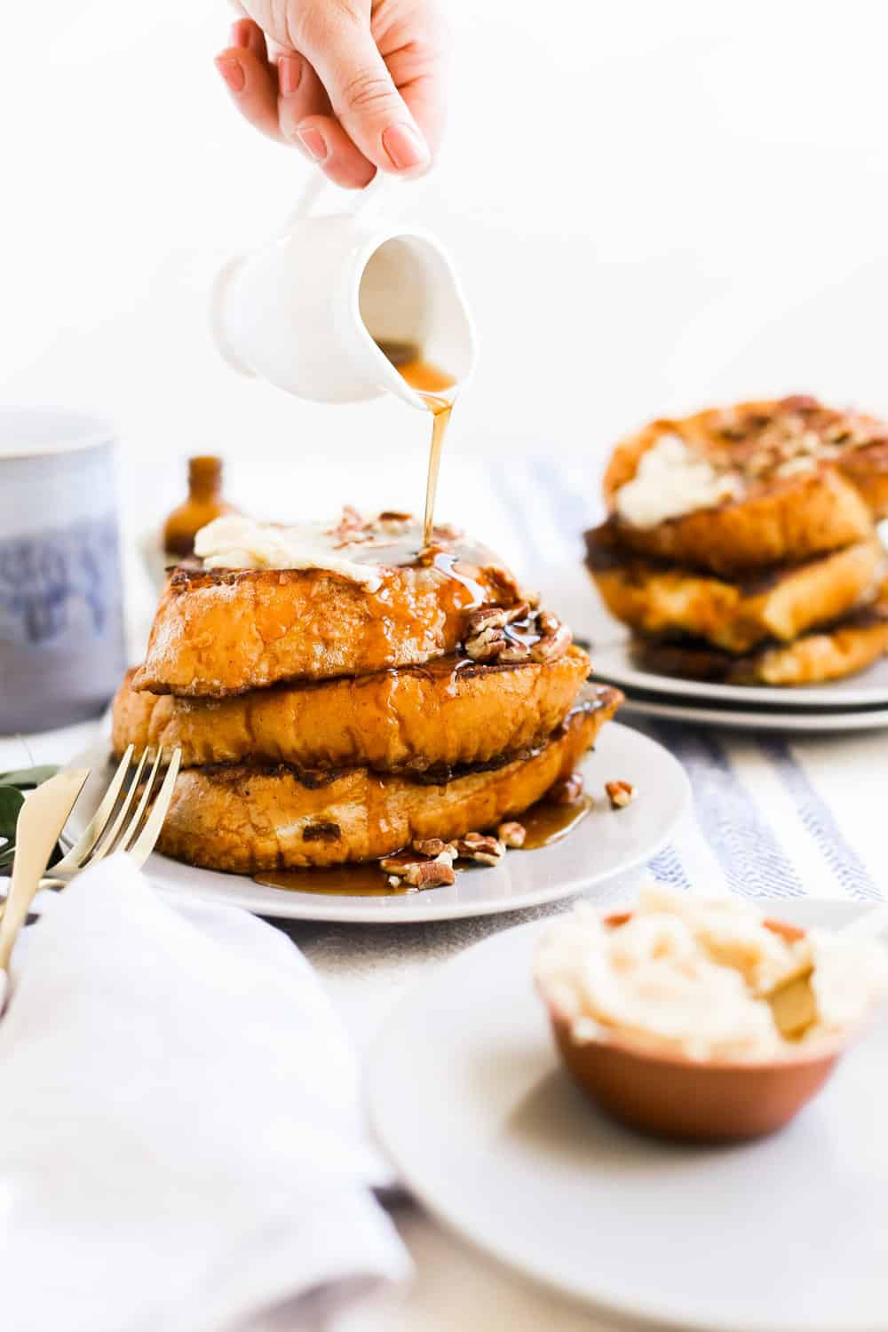 A stack of Pumpkin Spice French Toast on a plate with syrup being poured.