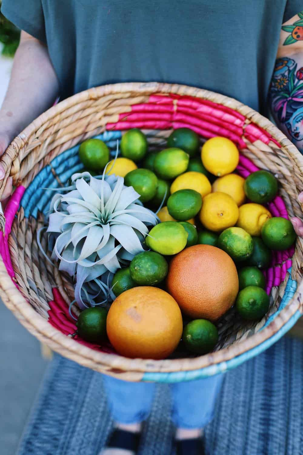Two hands holding a wicker basket full of grapefruit lemons and limes