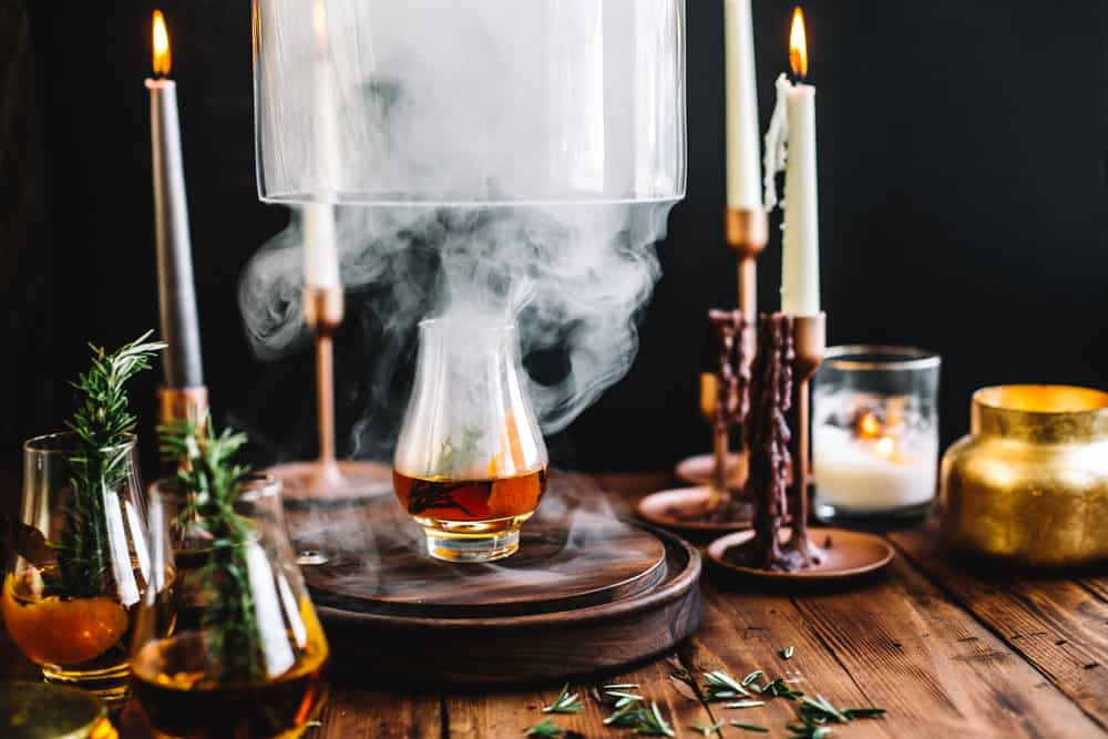 Smoking Cloche being lifted with a glass of Goblet of Fire garnished with a sprig of rosemary.
