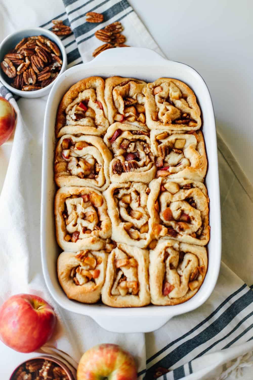 Baked apple pecan cinnamon rolls in a casserole dish.