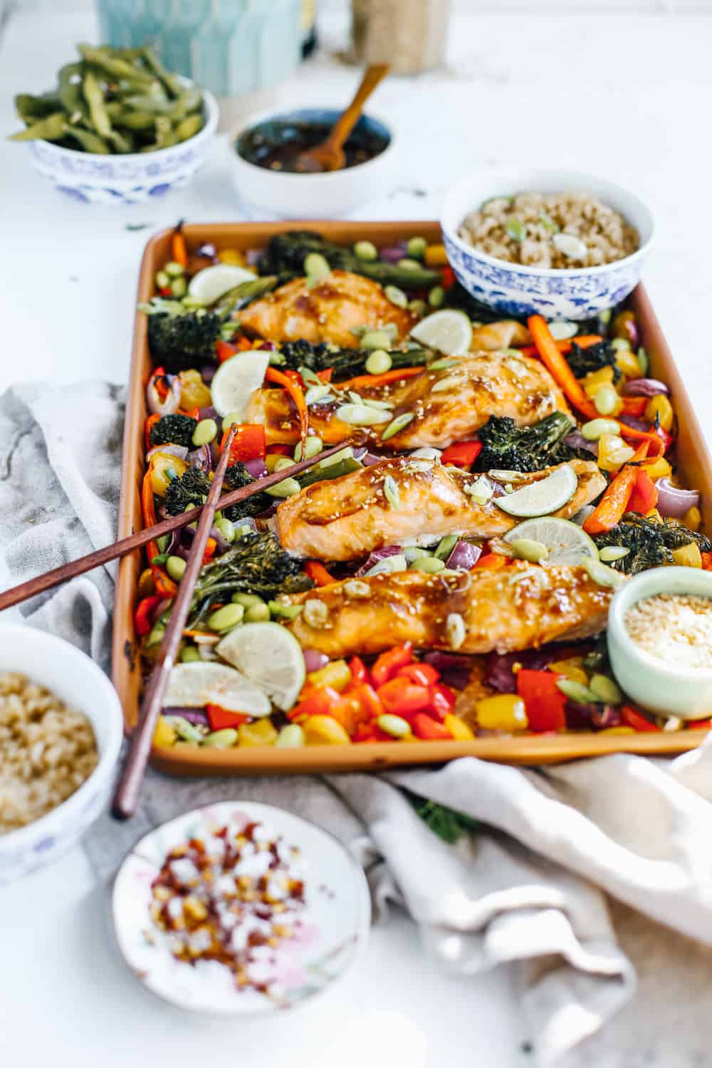 soy, garlic and ginger glazed salmon with broccolini, carrots, peppers and onions on sheet pan with chopsticks