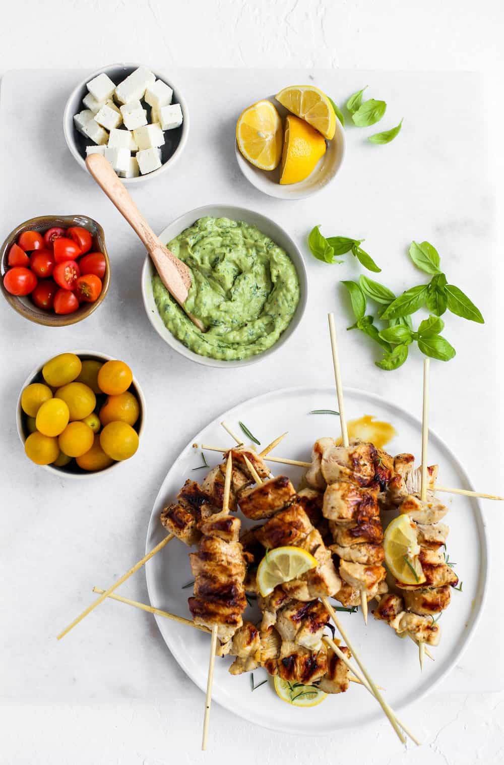 Lemon Garlic Chicken Skewer Bowls with green goddess dressing, tomatoes, feta, and lemons in a white bowl