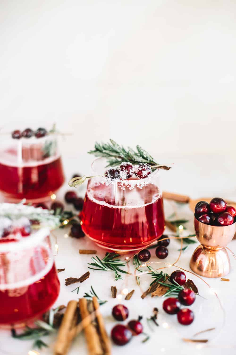 Low glass filled with a cranberry whiskey cocktails garnished with frosted cranberries and a rosemary sprig.