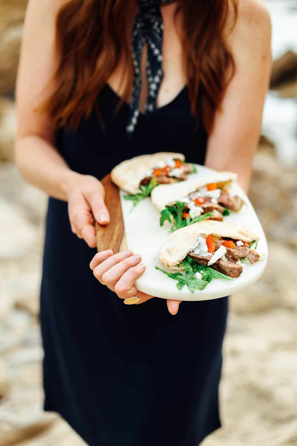 Elizabeth holding Garlic Lamb Pita Pockets on a cutting board on the beach