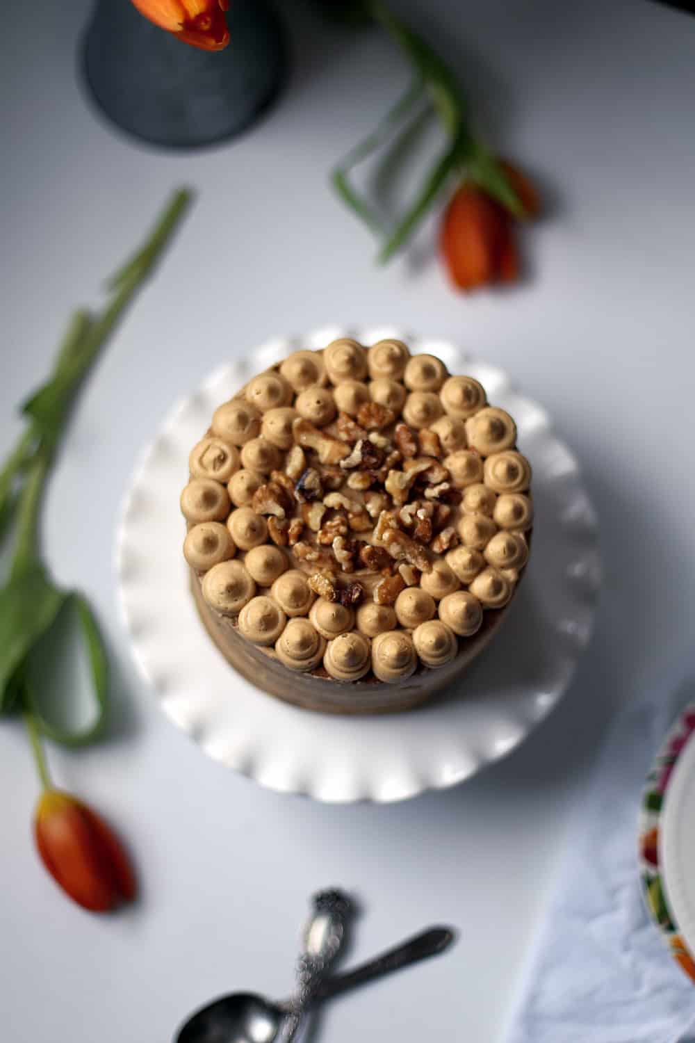 A coffee walnut cake frosted topped with walnuts.