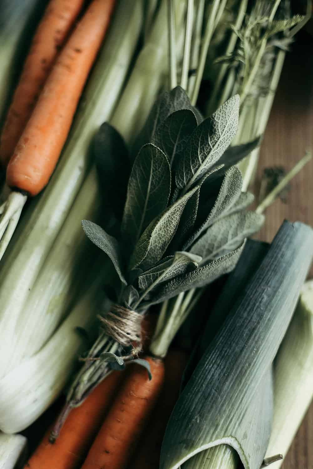 Leeks, carrots, celery, and bundled sage on a wooden cutting board.