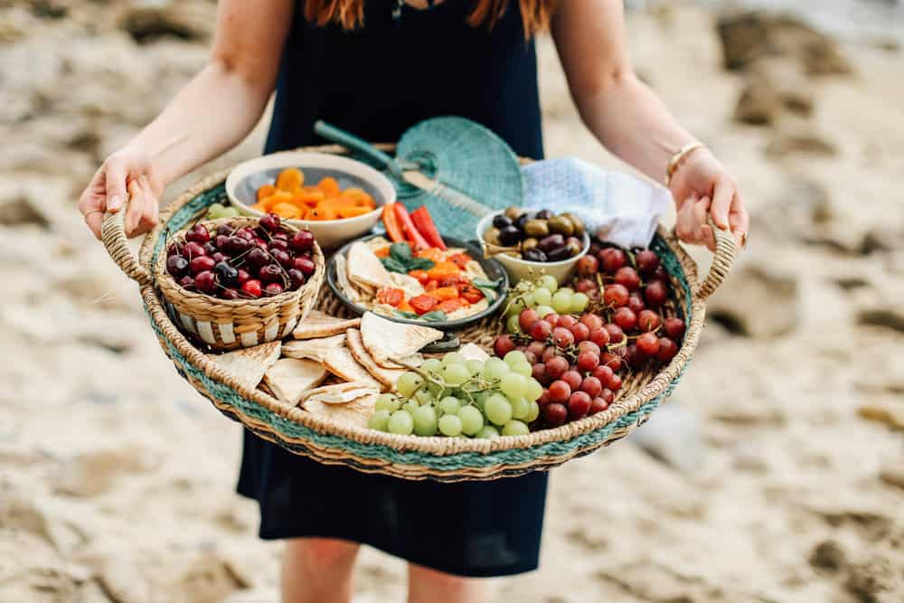 Elizabeth holding a basket full of grapes pita cherries apricots hummus and olives on the beach