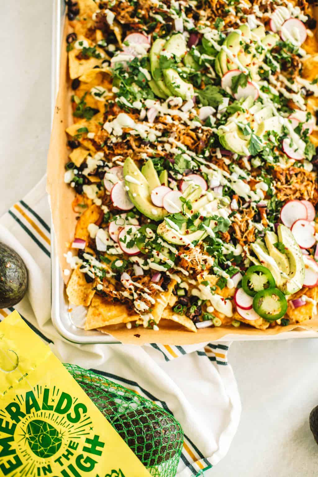 Insanely flavorful and juicy Jacuzzi chicken nachos. These nachos are topped with shredded chipotle Jacuzzi chicken and avocado crema + all the toppings!