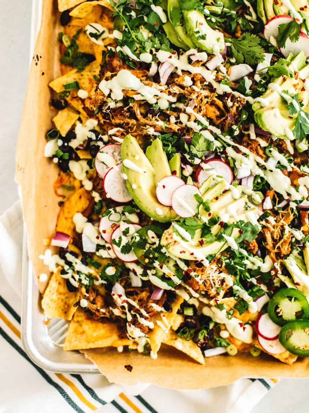 Insanely flavorful and juicy Jacuzzi chicken nachos. These nachos are topped with shredded chipotle Jacuzzi chicken and avocado crema + all the toppings! Did someone say Super Bowl food coma!?