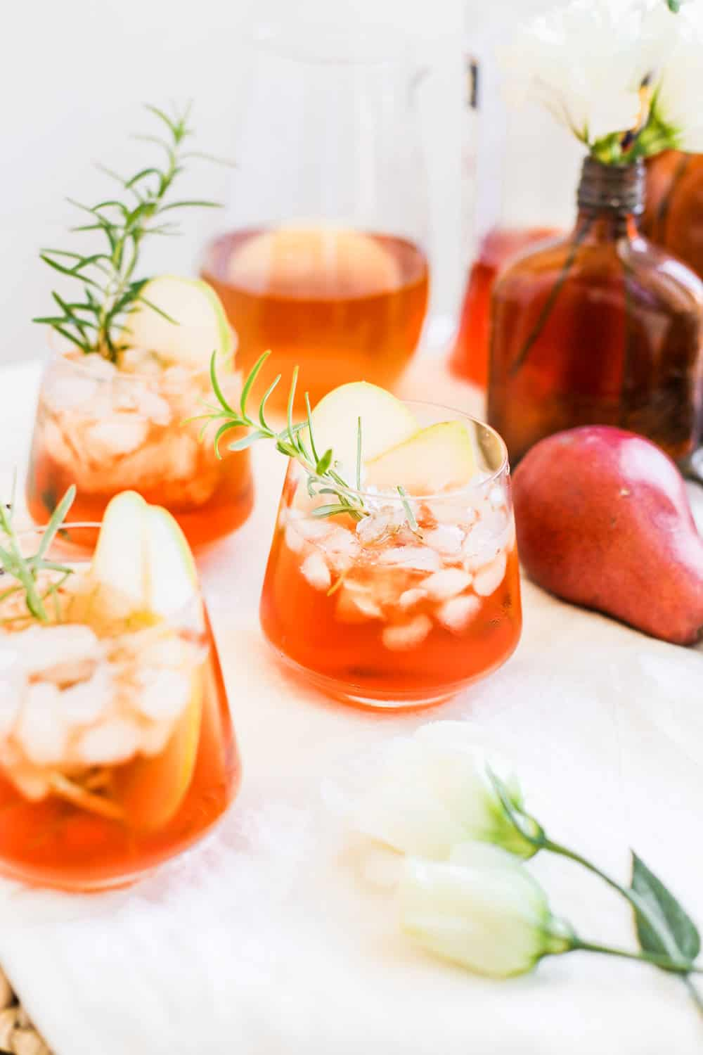 A low clear glass filled with aperol and hard cider with a rosemary sprig.