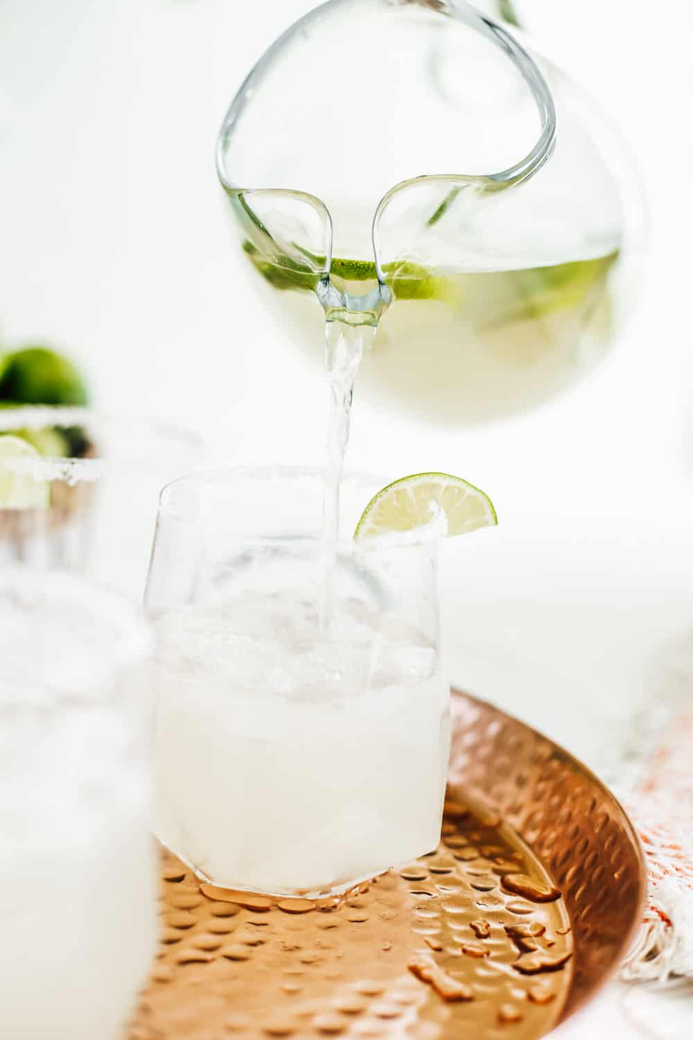 A low clear glass, being filled by a pitcher of a classic margarita on a copper tray.