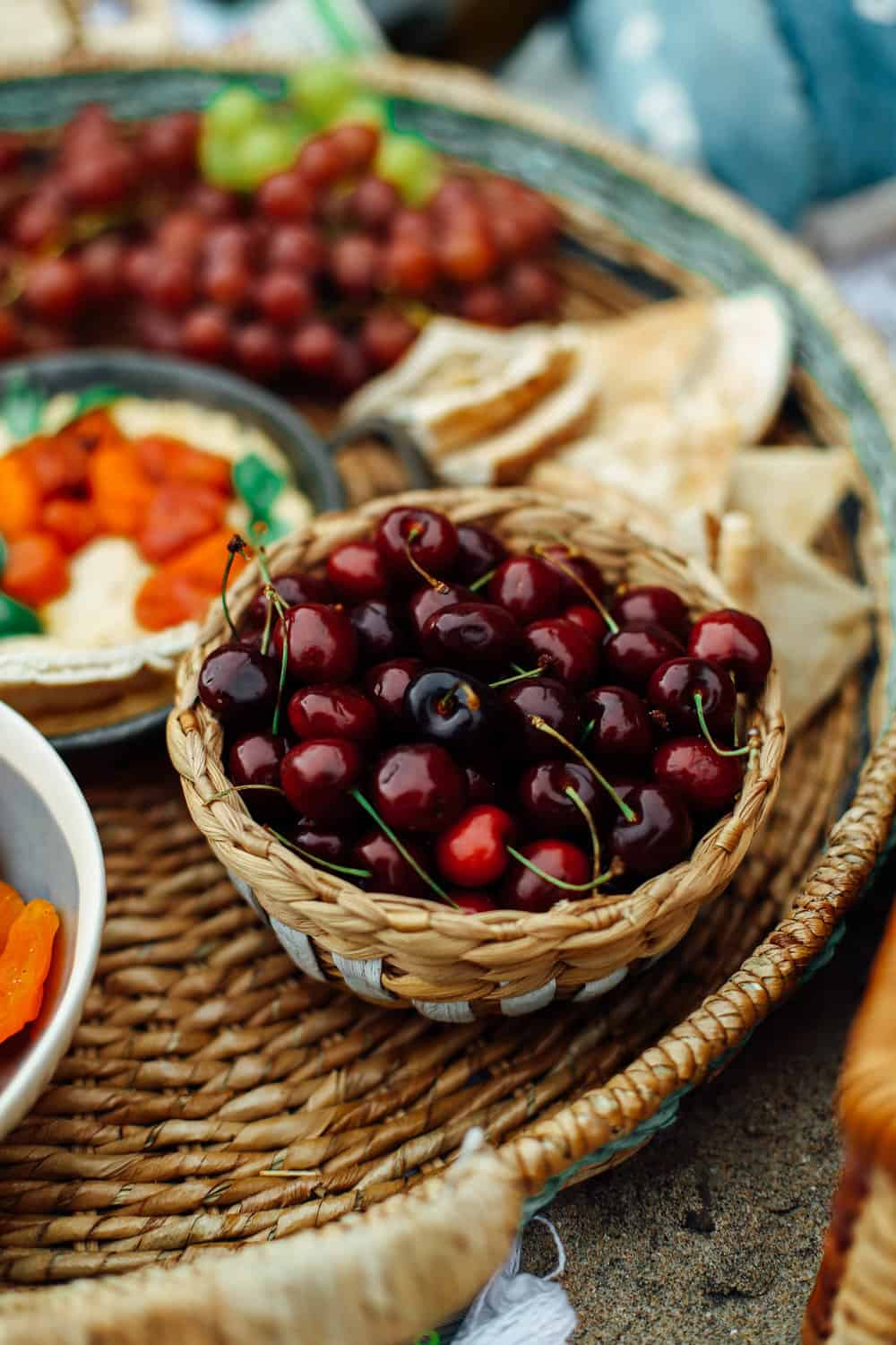 Cherries in a picnic bowl with pita hummus and grapes in a wicker basket