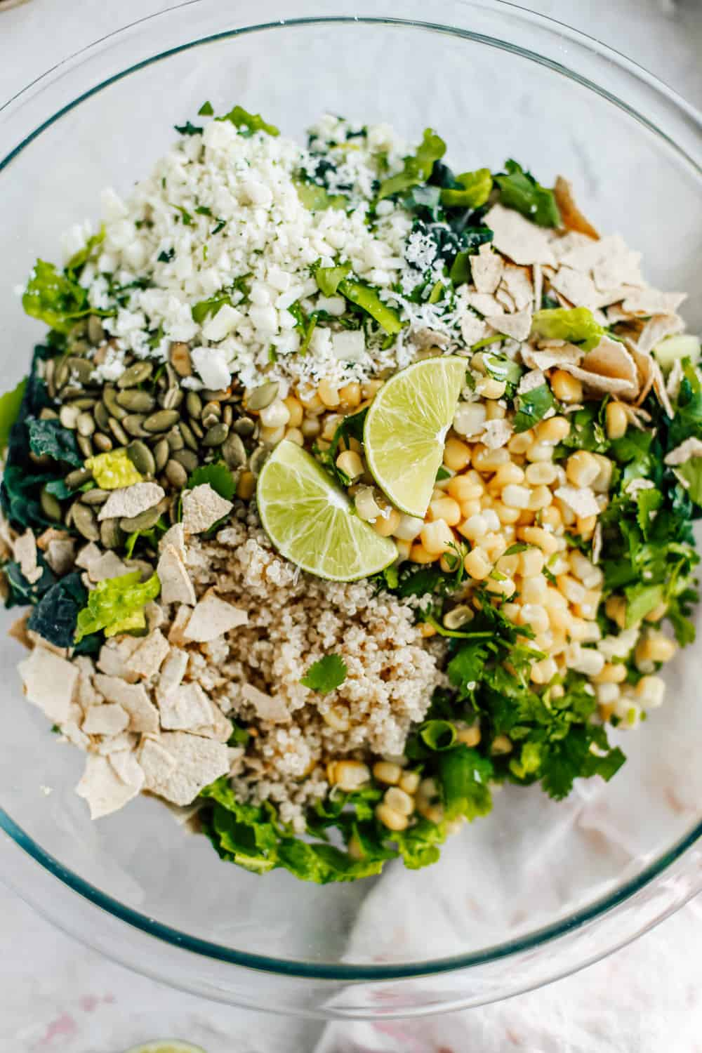 Kale Romaine Golden Corn Quinoa Cilantro and Lime Ingredients in a Clear Mixing Bowl