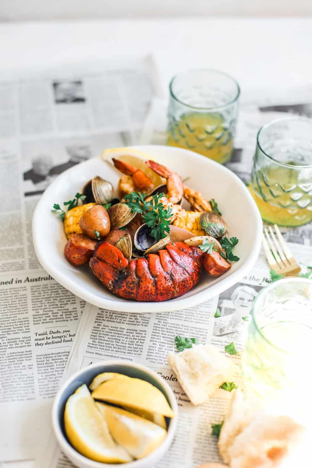 lobster tails, shirmp and clams in white bowl with lemon wedges