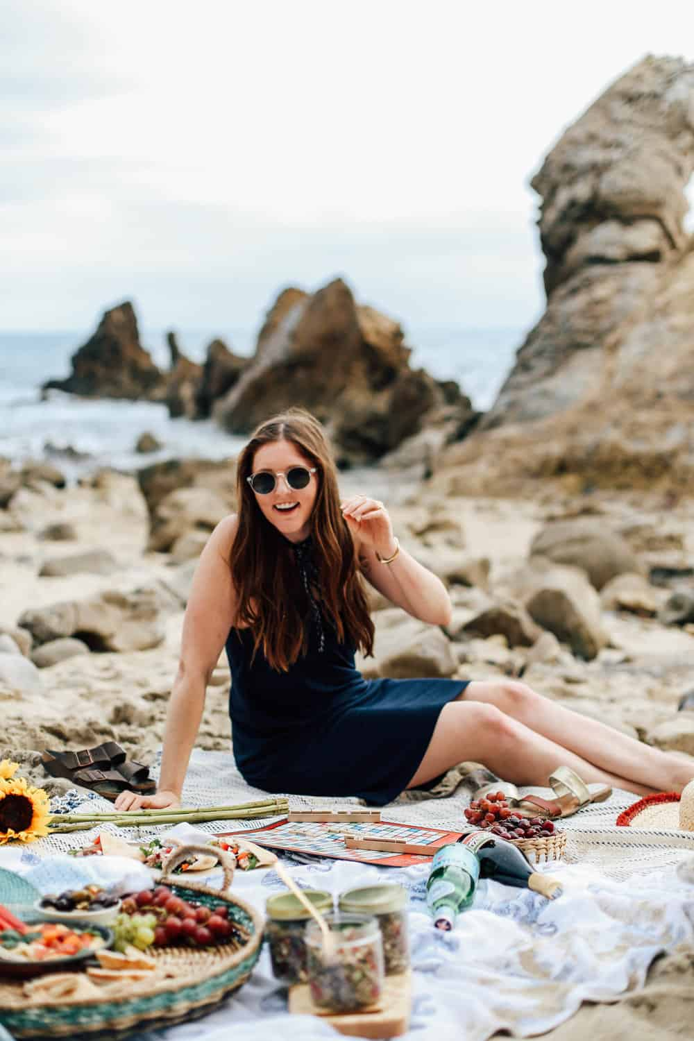 Elizabeth sitting on beach towels with beach food and Scrabble game board on the beach