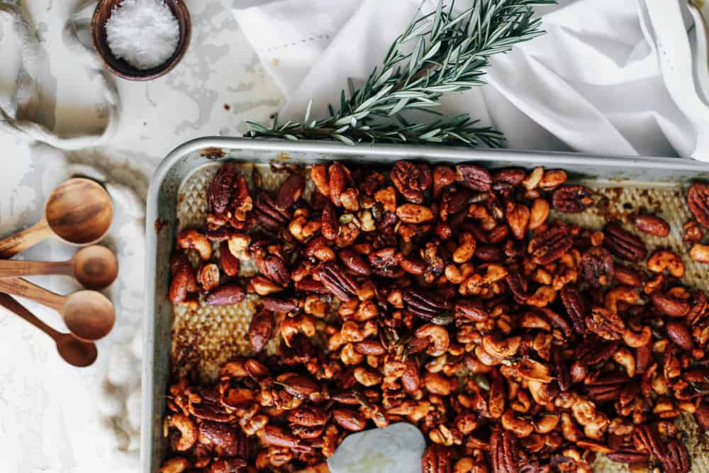Baked mixed nuts on a large baking sheet.