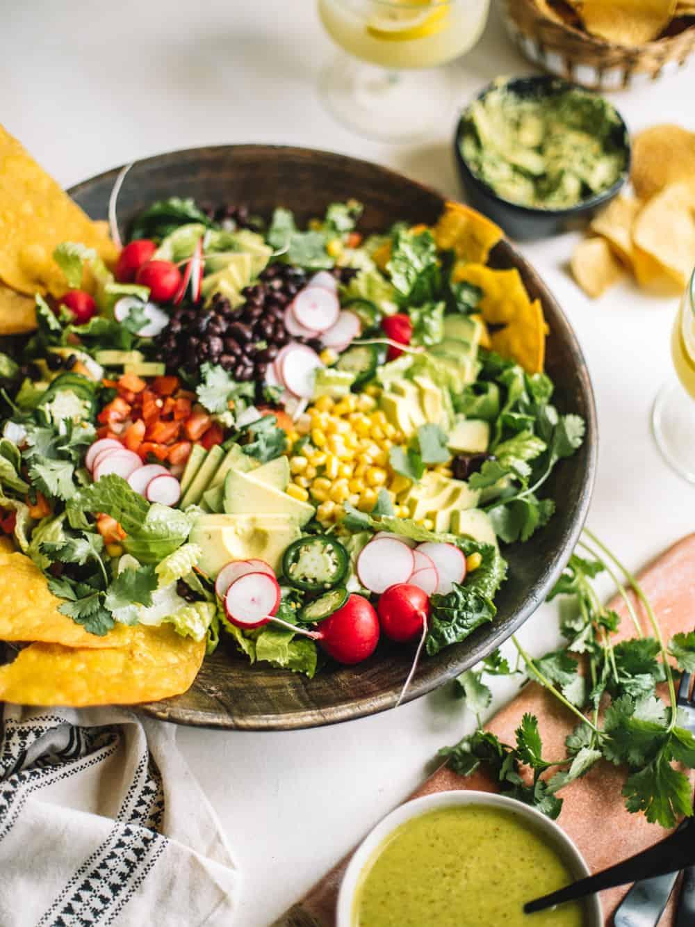 A big wooden bowl of Chopped Tostada Salad with Avocado Cilantro Dressing