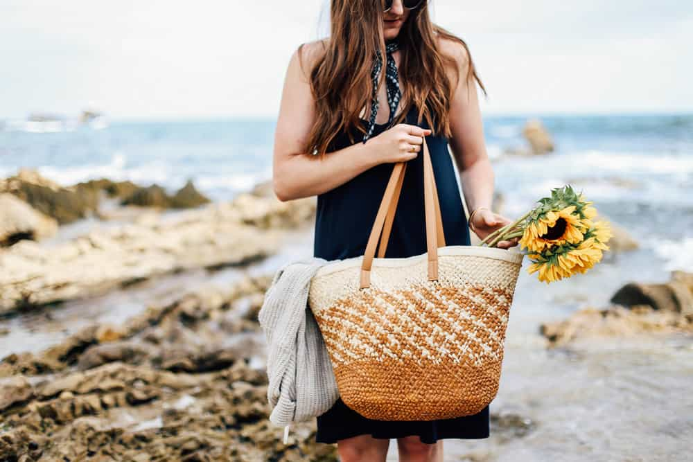 Elizabeth carrying a beach bag with sunflowers on the beach