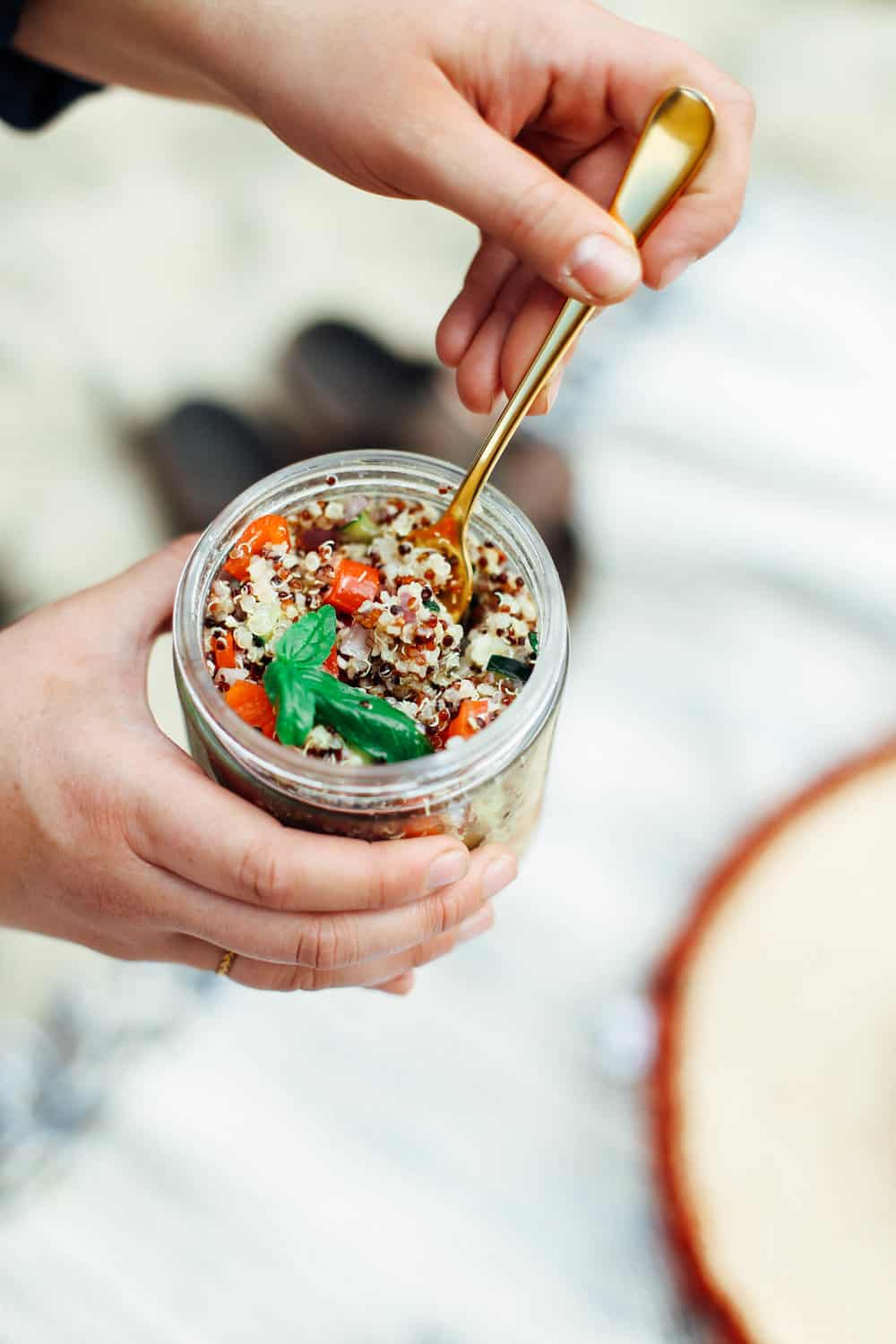 Elizabeth holding the Lemon Quinoa Side Salad in a mason jar with a gold fork