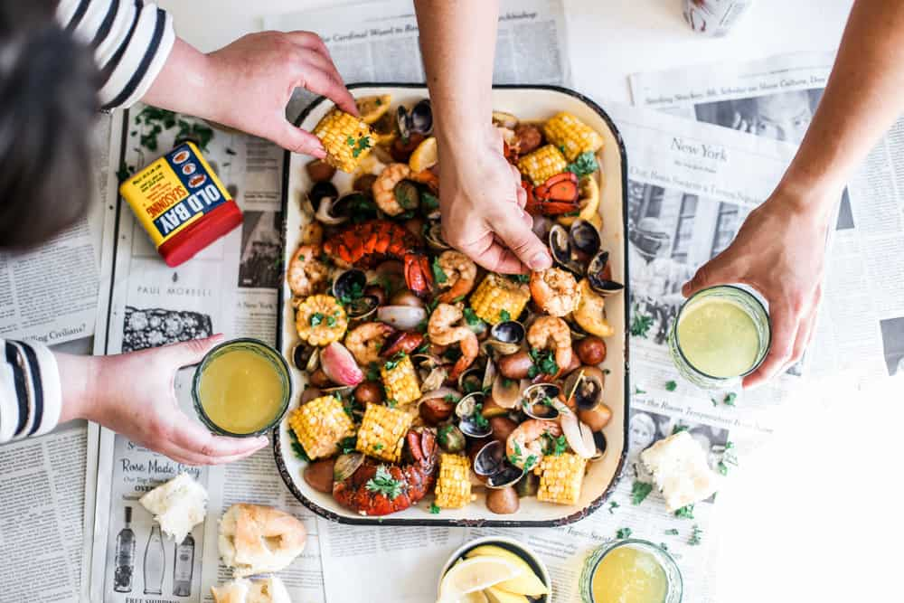 hands touching clams, shrimp, lobster, potatoes, corn on sheet pan with old bay and melted butter