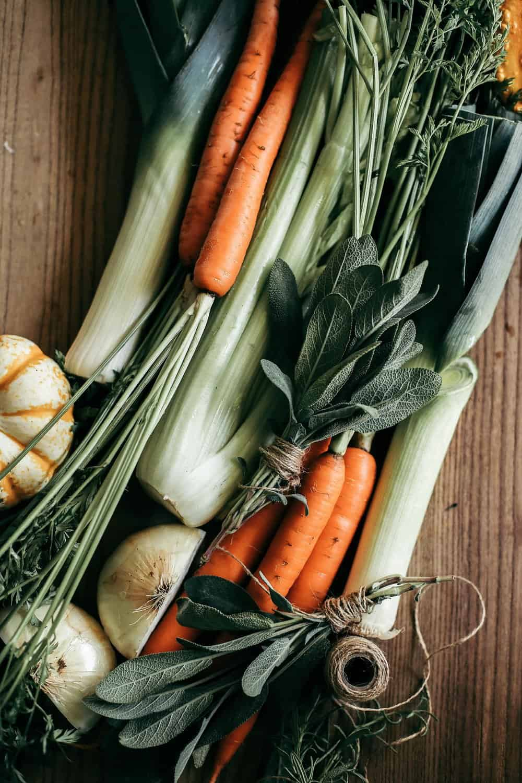 Carrots, celery, onions, leeks, bundled sage on a wooden cutting board.
