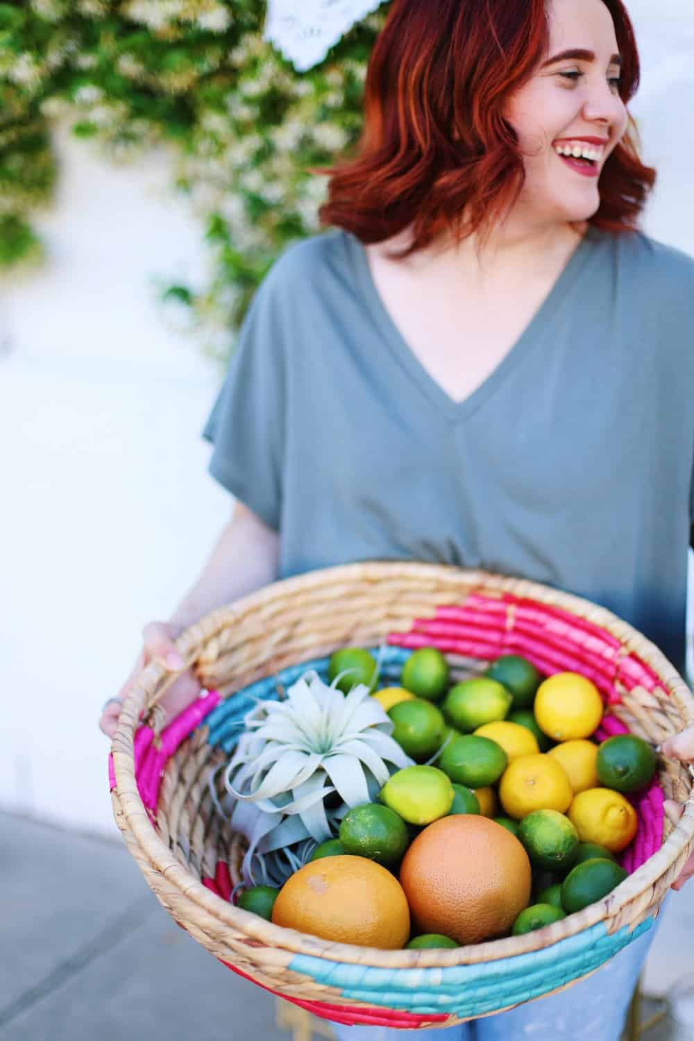 Two hands holding a wicker basket filled with grapefruits lemons and limes