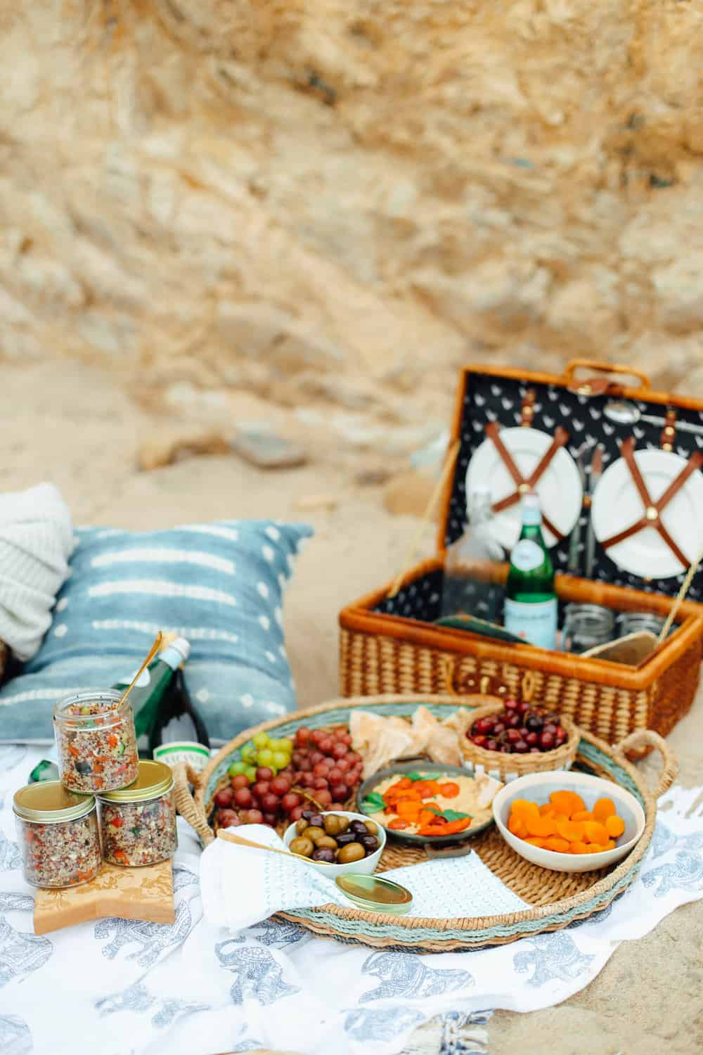 Grapes Pita Cherries Apricots Olives and Hummus in a wicker basket and sparkling water glasses and plates in a picnic basket with towels on the beach
