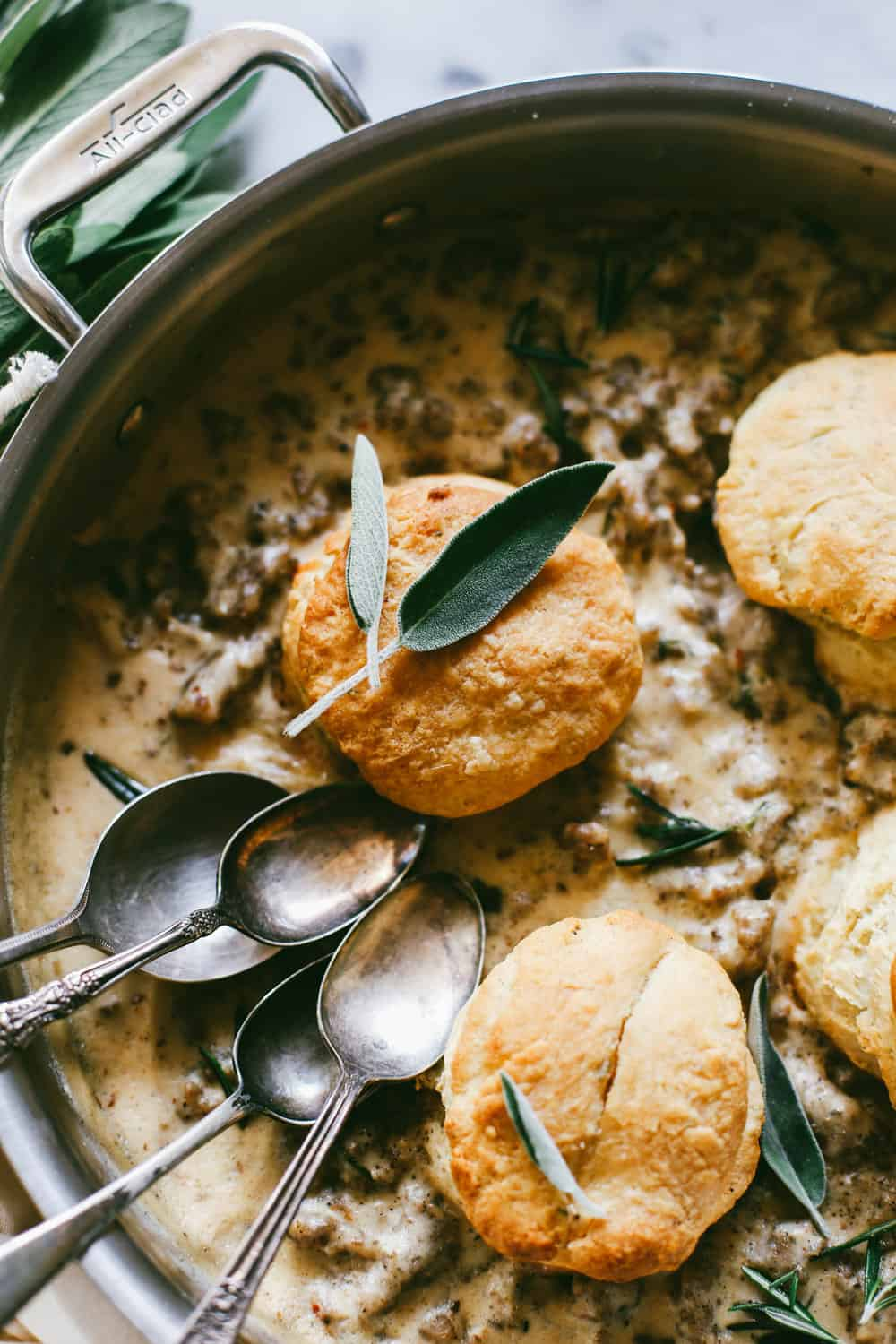 Bourbon Biscuits and Sage Sausage Gravy in a pan with spoons.