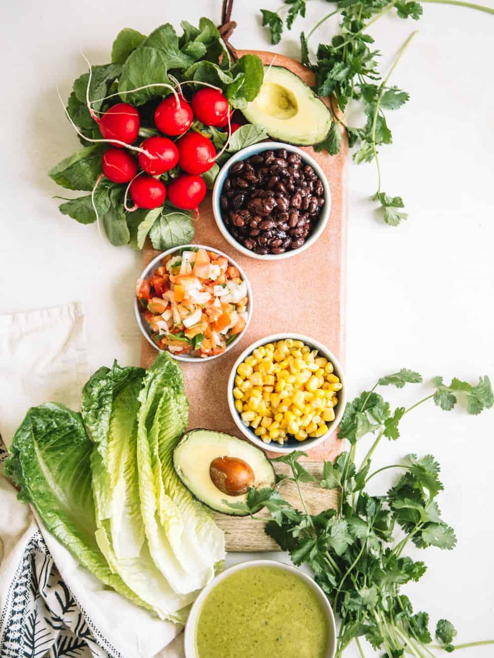 Small bowls of corn, black beans, pico de galla, radishes, and cliantro.