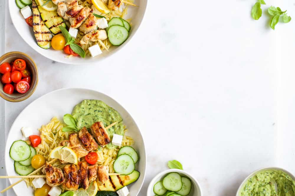 Lemon Garlic Chicken Skewer Bowls with orzo and green goddess dressing in a white bowl