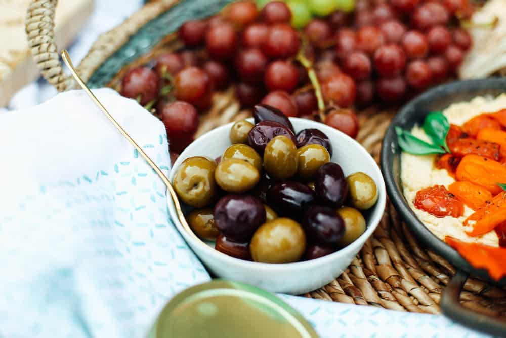 Mediterranean Olives in a white bowl with grapes and hummus in a wicker basket