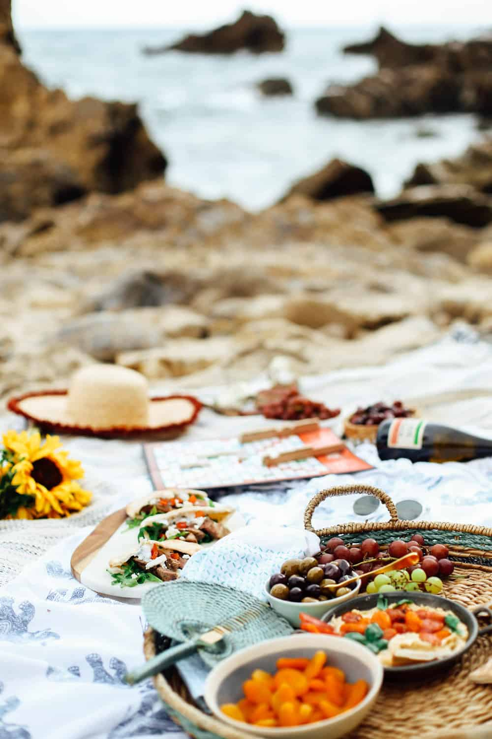 Mediterranean beach picnic spread with lamb pita pockets grapes olives hummus wine and Scrabble game board on beach towels on the beach