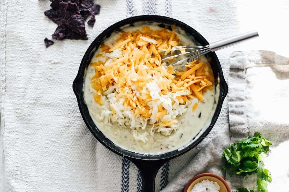 A skillet filled with cheese being whisked.
